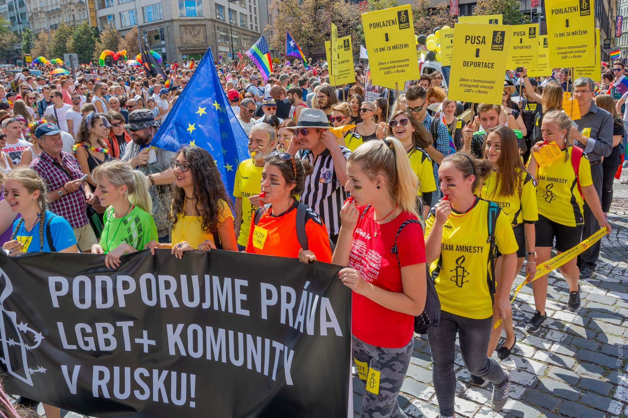 Надпись на жёлотом транспаранте: «Поцелуй → Депортация — закон о гомосексуальной пропаганде ограничивает права ЛГБТ сообщества в России».